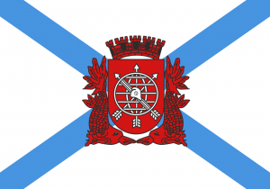 The flag of the city of Rio de Janeiro - a red seal centered on a white background with two crossing blue stripes
