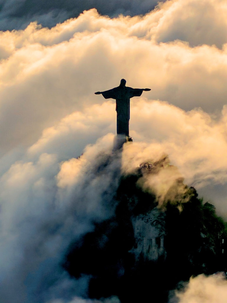 Christ the Redeemer just above the clouds at golden hour