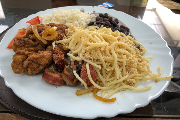 Fried chicken, sausage, rice/beans, pasta with a dried pea/fried onion mixture, and tomatoes
